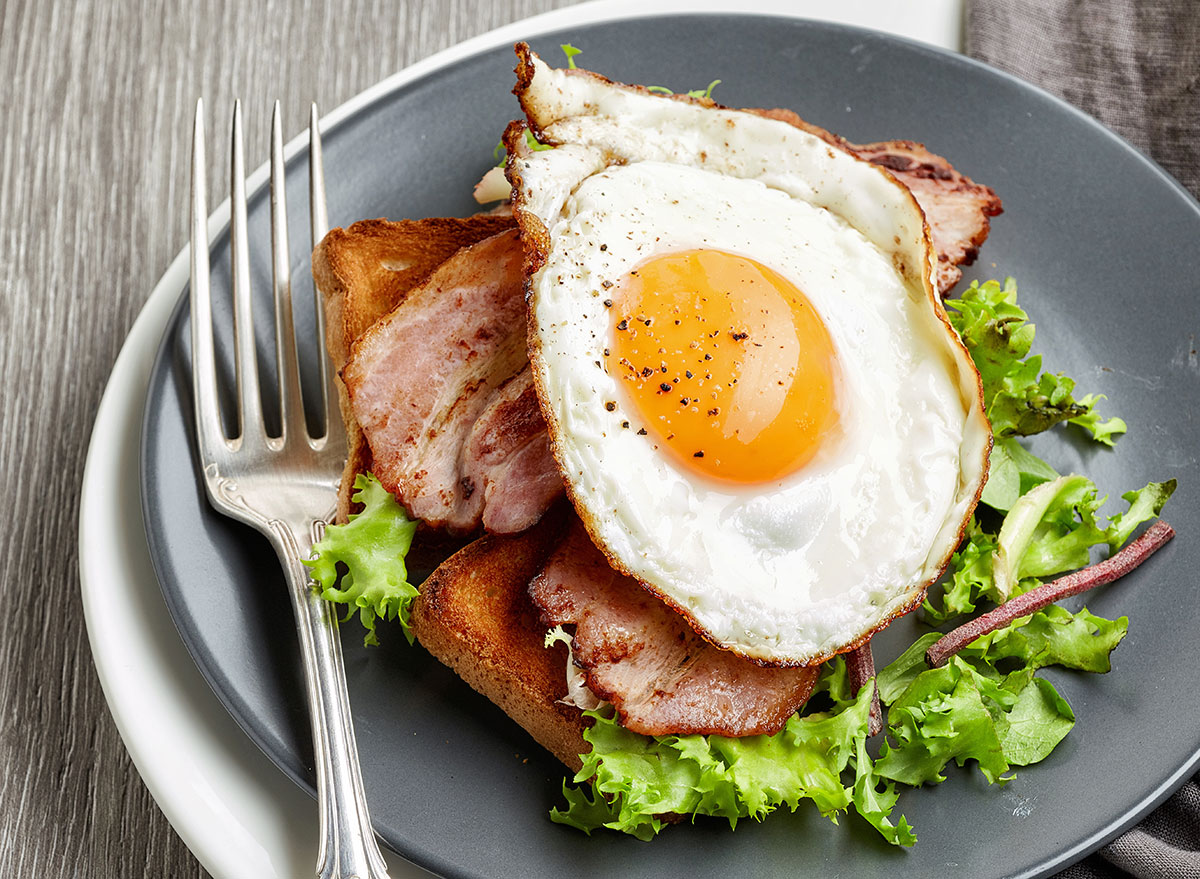 Fried egg on a blt sandwich on gray plate with fork